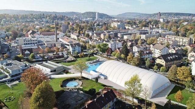 Blick auf eine Anlage mit grünen Wiesen, über einem Schwimmbad ist ein weisses Zelt gespannt.