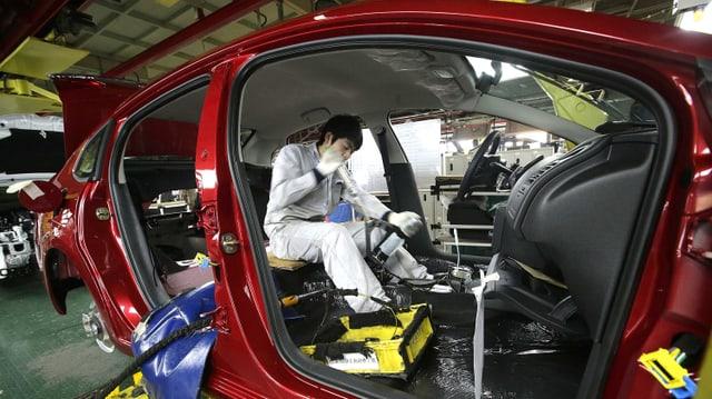 Blick in einen Peugeot in der Fertigungsstrasse. Ein Arbeiter montiert innen liegende Werkteile.