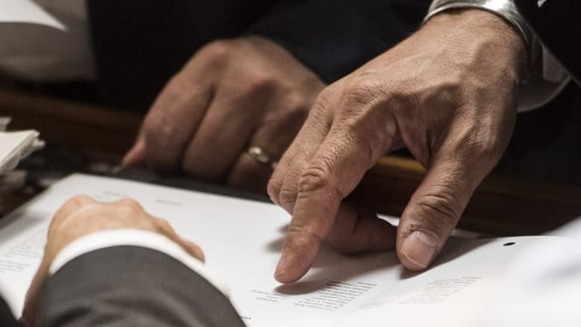 Drei Männer zeigen auf Dokumente