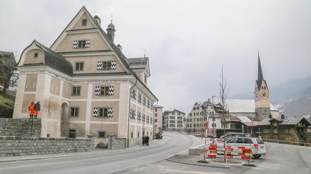 L'entrada dal vitg da Trun cun las duas chasas marcantas museum e chasa Carigiet ch'e brischada.