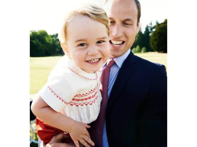 Prinz George in die Kamera grinsend. Prinz William hält ihm auf dem Arm.