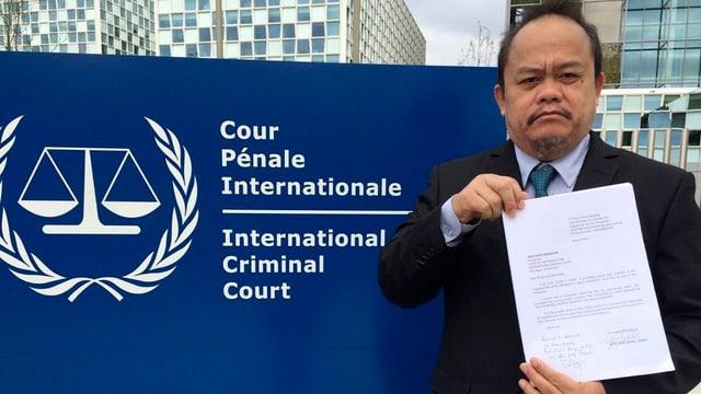 Ein Mann mit einem Schreiben in der Hand vor dem Schild des Internationalen Strafgerichtshofs.
