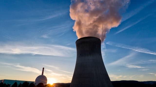 Blick auf das Atomkraftwerk Leibstadt im Gegenlicht vor blauem Himmel mit dem Kühlturm, aus dem Wasserdampf aufsteigt.