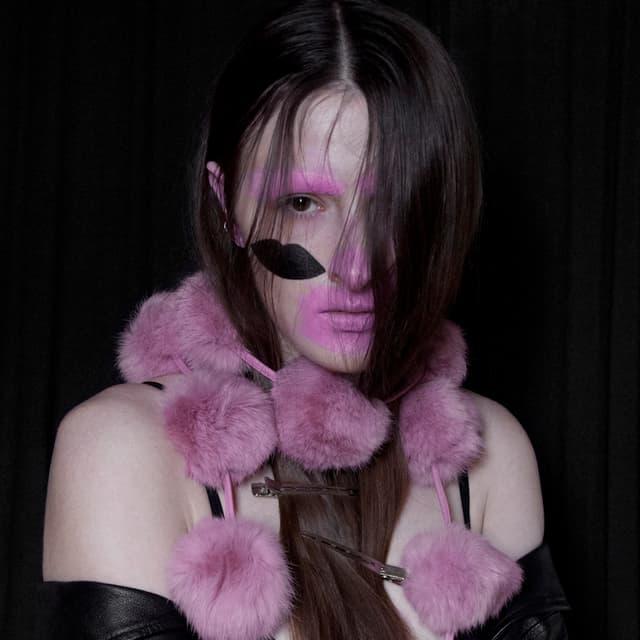 Eine junge Frau trägt ihre Haare zur Hälfte im Gesicht, ihre Augenbrauen sind rosarot geschminkt, ebenso ein grosser Bereich um ihre Lippen. Auf ihre sichtbare Wange ist eine schwarze Lippe gemalt.