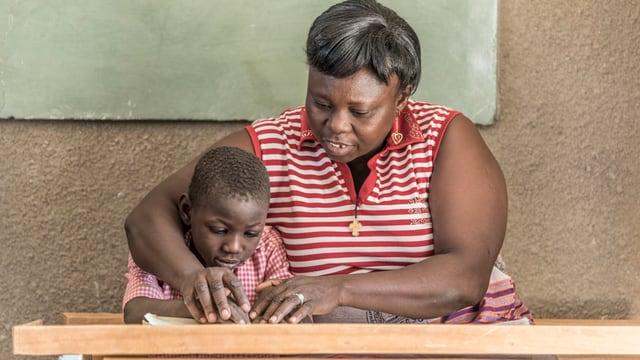Eine Kindergärtnerin kümmert sich um ein Kind im Kindergarten in Burkina Faso