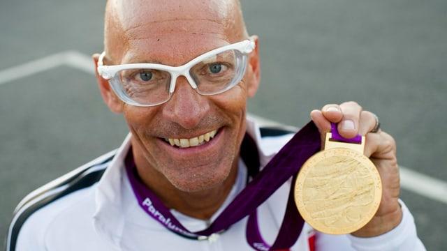 Mann mit Glatze, Sportbrille und Goldmedallie.