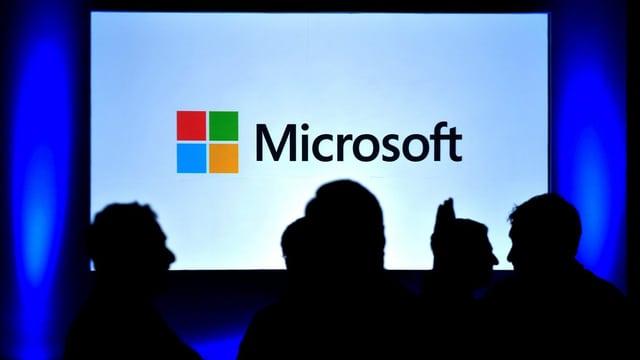 Microsoft-Logo auf einem Bildschirm, einige Menschen davor.