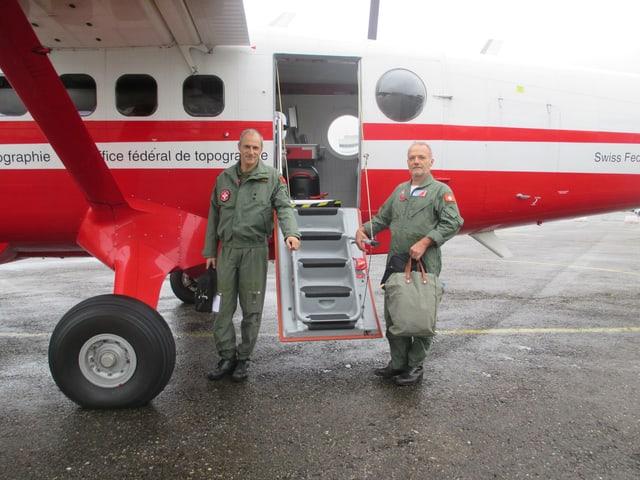 Zwei Männer in Fluguniform vor einem rot-weissen Flugzeug