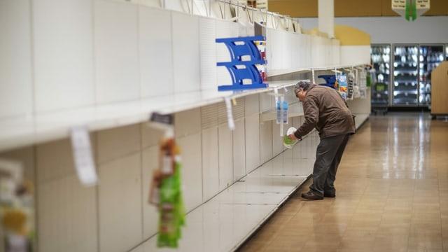 Ein Mann nimmt sich in letztes verbliebenes Paket in einem ansonsten leeren Regal.
