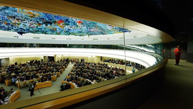 Blick durch ein Fenster in einen grossen, runden Plenarsaal.