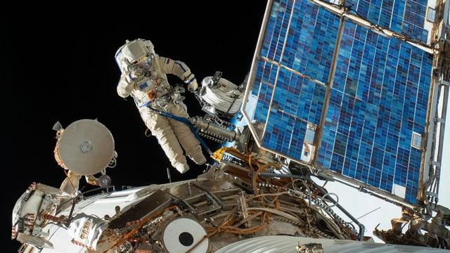Ein Kosmonaut schwebt vor einer Raumstation im Weltall