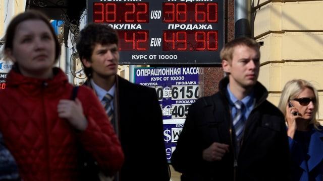 Passanten in Moskau vor einer Tafel mit Rubelkursen