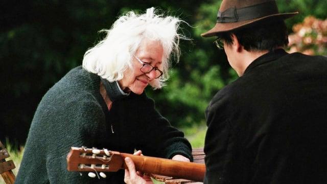 Eine alte Dame hört einem Mann beim Gitarre spielen zu.