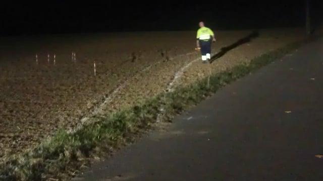 Dunkelheit. Rechts ein schmaler Weg, links in einem Feld Autospuren.