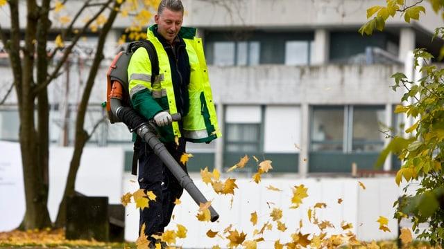 Mann mit Laubbläser und Herbstblättern