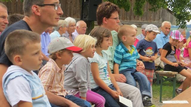 Bauernfamilie mit Kindern bei der Messe im Freien