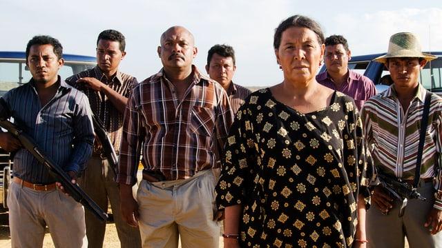Ältere Frau, hinter ihr stehen sechs bewaffnete Männer