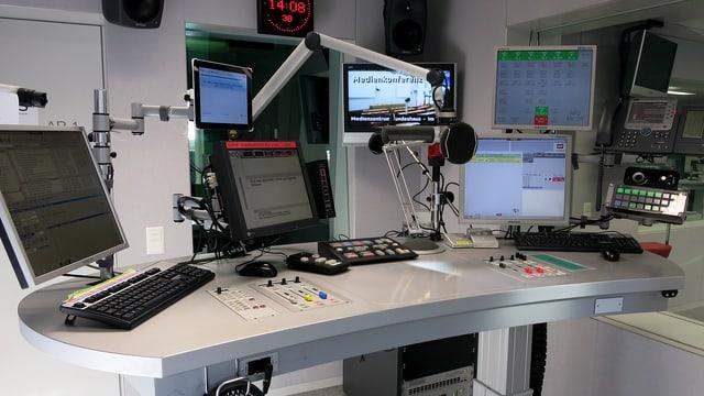 Pult mit Mikrofon und mehreren Bildschirmen