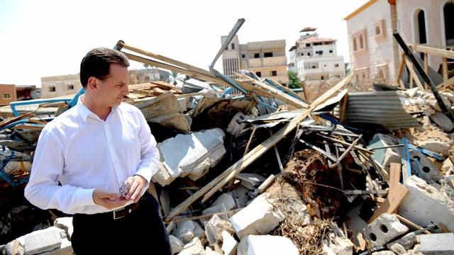 Mann mit weissem Hemd steht vor Trümmern.
