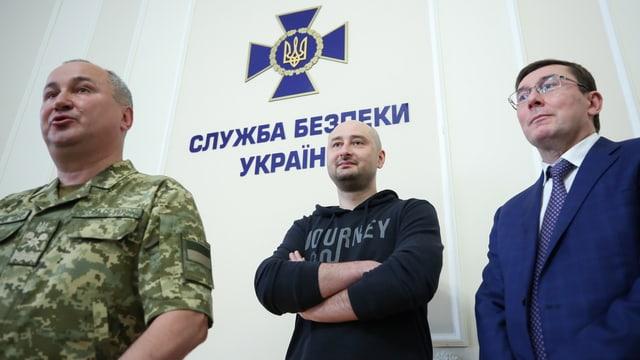 Babtschenko neben einem Mann in Uniform und einem im Anzug.