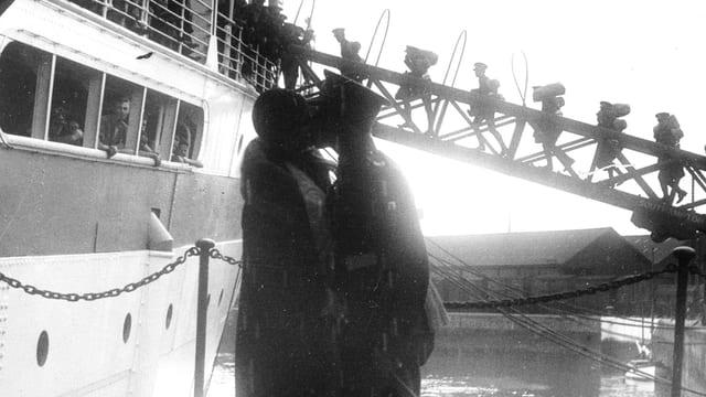 Ein Pärchen küsst sich. Er trägt Uniform. Im Hintergrund: Ein Schiff und Soldaten, die das Schiff besteigen.