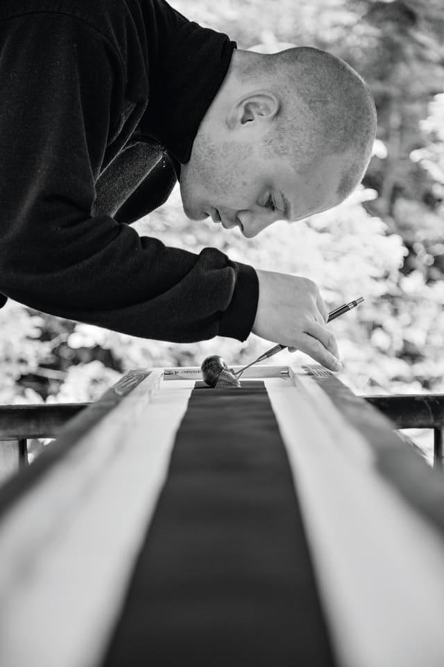 Ein Künstler beugt sich über eine lange Fläche, auf der er mit einer Pinzette eine Schnecke platziert.