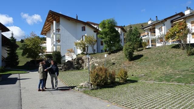Drei Leute stehen inmitten einer Feriensiedlung mit weissen Gebäuden.