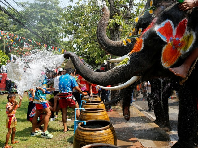 Kind wird von Elefanten nass gespritzt.