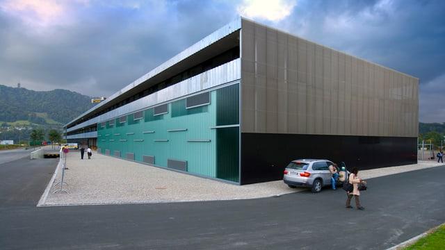 modernes Schulgebäude, im Hintergrund der Üetliberg