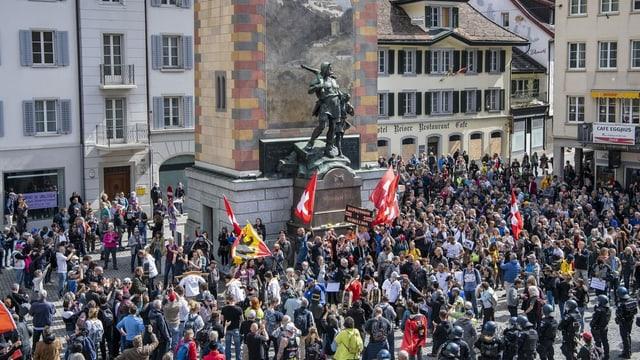 Personen stehen um das Telldenkmal herum