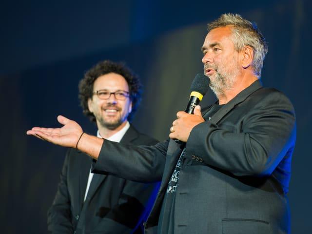 Besson spricht auf der Bühne in ein Mikrofon, Chatrian steht lachend daneben.