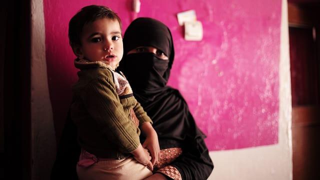 Schwarz verhüllte Frau mit Kind auf dem Arm vor rosa Wand.