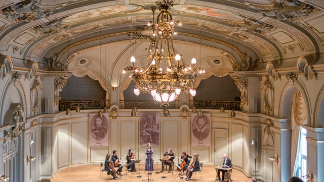 Grosse Halle mit Kronleuchter und fünf Geigenspielern in der Mitte
