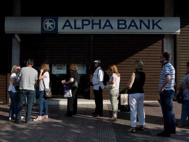 Menschen stehen Schlange vor einer Bank.