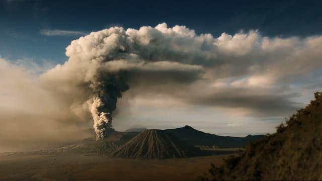 Ein Vulkan bei der Eruption mit grosser Rauchwolke.