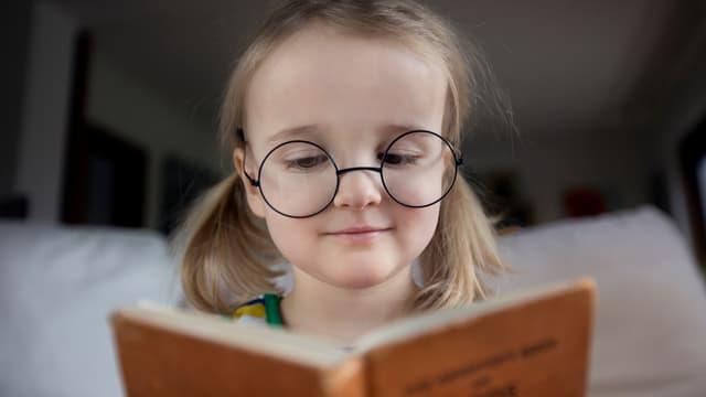 Kleines Mädchen mit Brille liest ein Buch.