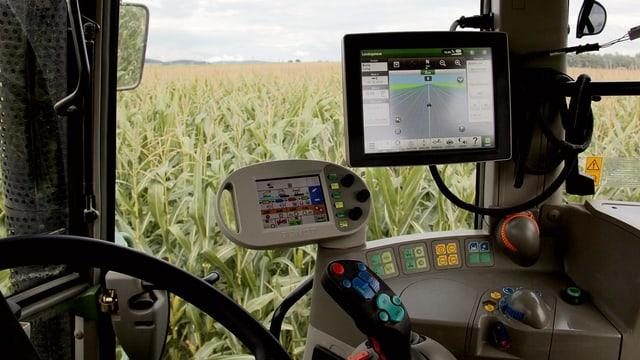 Blick aus dem inneren eines computerassistierten Traktors. Man sieht einen kleinen Bildschirm, auf dem digital die Spuren zu sehen sind, denen der Traktor automatisch folgt.