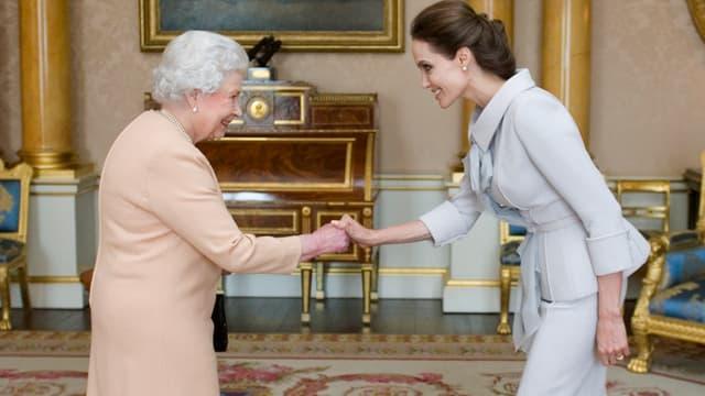 Die Queen und Angelina Jolie reichen sich die Hände.