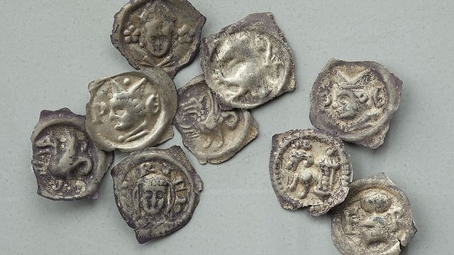 Silbrige Münzen aus dem Fund, sie sind nicht ganz rund, sondern weisen echikge Kanten auf