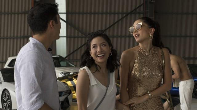 Zwei Frauen, eine davon im Glitzeranzug, lachen, ein Mann steht daneben.