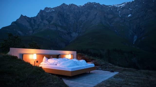 Ein Bett unter freiem Himmel. Zwei Menschen liegen im Bett.