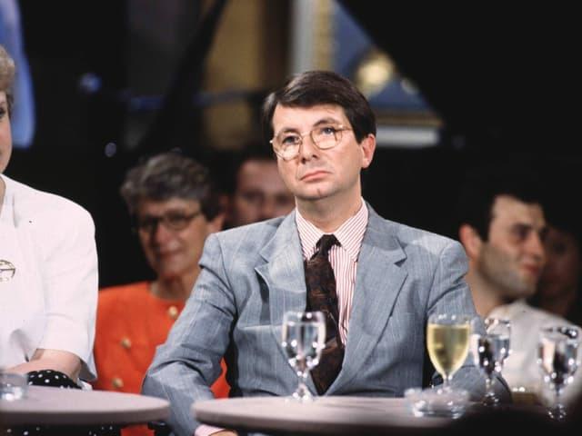 Mann mit Brille und Anzug im Stil der 1990er-Jahren sitzt an einem Tisch. Vor ihm ein Wasserglas.