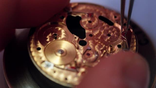 Uhrmacher mit Pinzette.