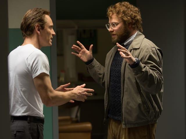 Zwei Männer im Gespräch, mit den Händen gestikulierend.