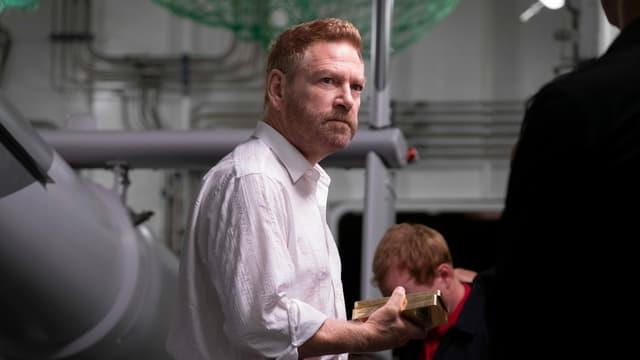 Szene: Andrei Sator (Kenneth Branagh) hält zwei Goldbarren.