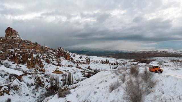 Ein Auto fährt durch eine Winterlandschaft.