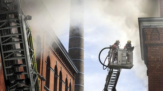 Feuerwehrmänner auf Drehleiter mit Schlauch in Fabrikareal mit viel Rauch