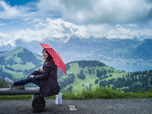 Asiatische Touristin mit Sonnenschirm auf der Rigi - im Hintergrund Berge und Vierwaldstättersee.