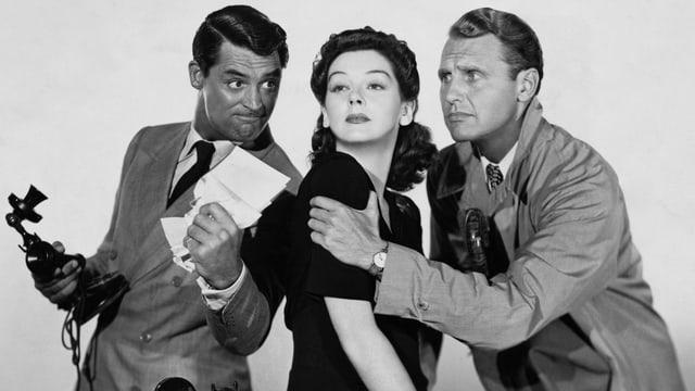 Man sieht Rosalind Russell. Sie ist umgeben von Cary Grant und Ralph Bellamy.