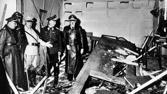 Schwarz-weisses dokumentarisches Foto: NS-Soldaten vor den Trümmern eines Tisches.